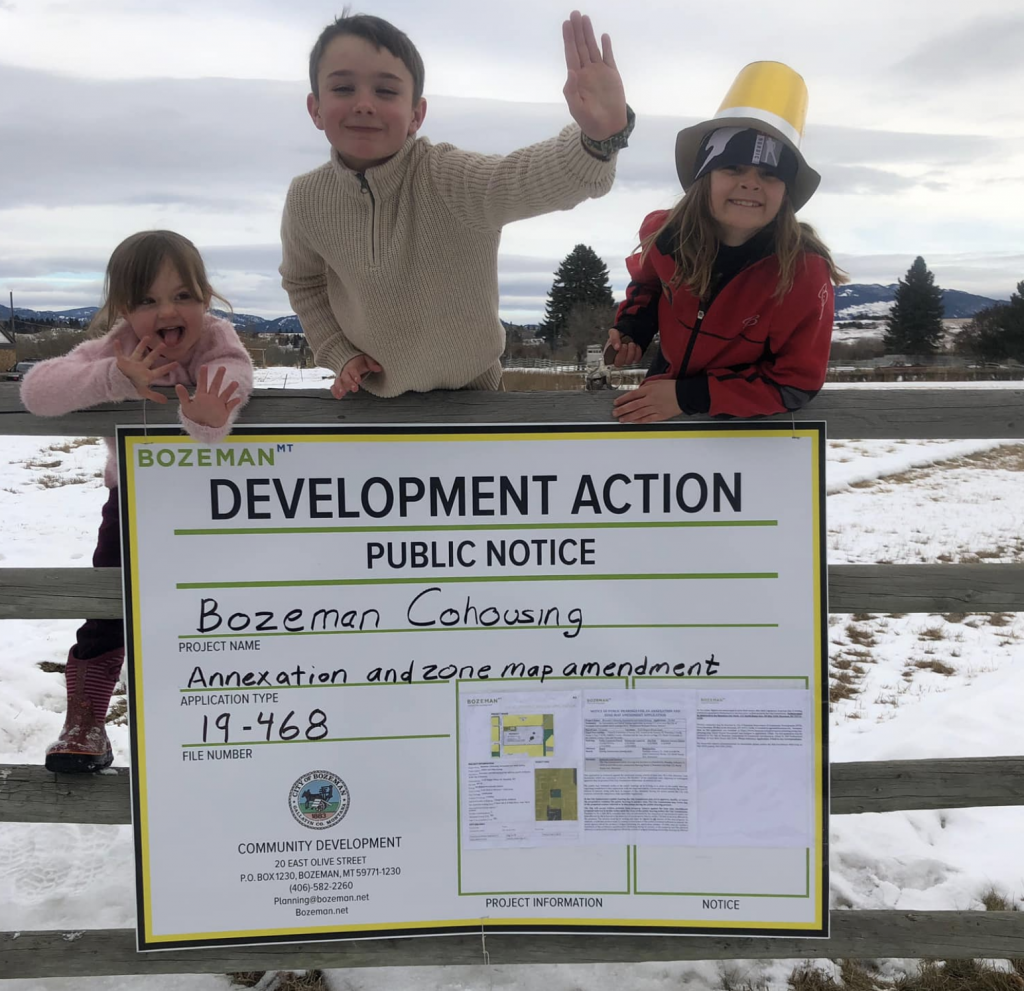 Children helping to post development sign.